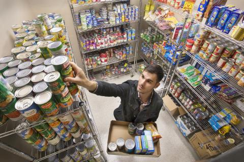 A person stocking shelves filled with nonperishable food items